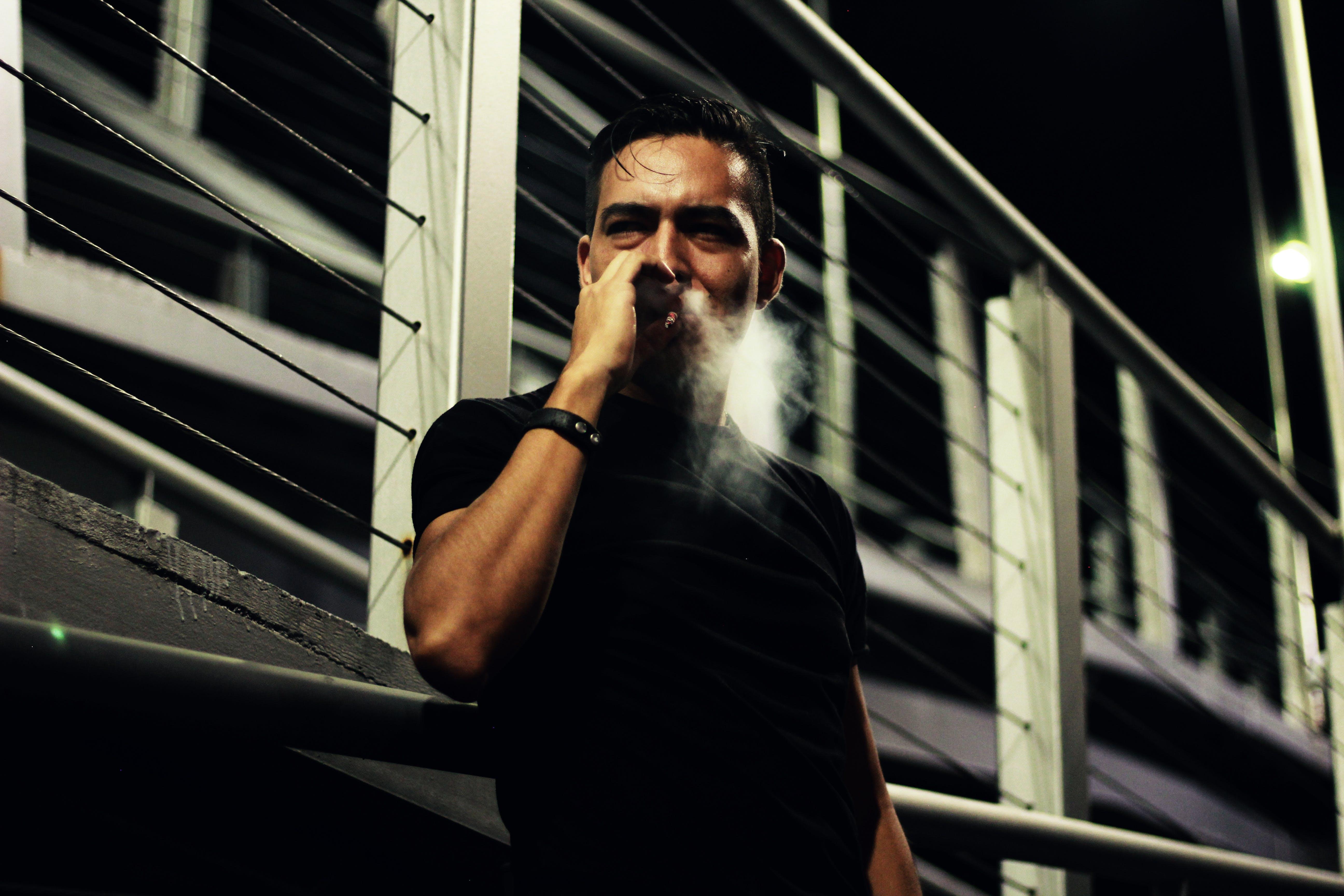 Man Smoking Near Bridge