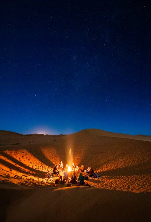 People Sitting in Front of Bonfire in Desert during Nighttime