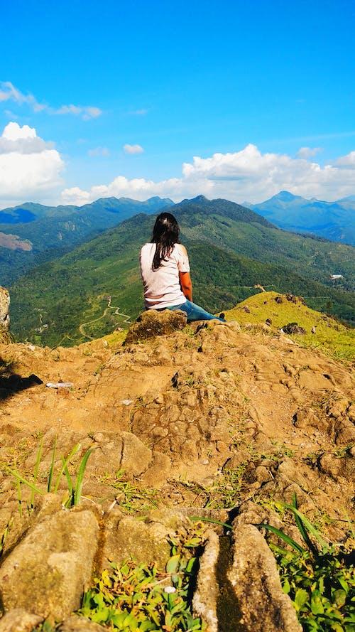 Gratis arkivbilde med jente sitter på klippen, landskap