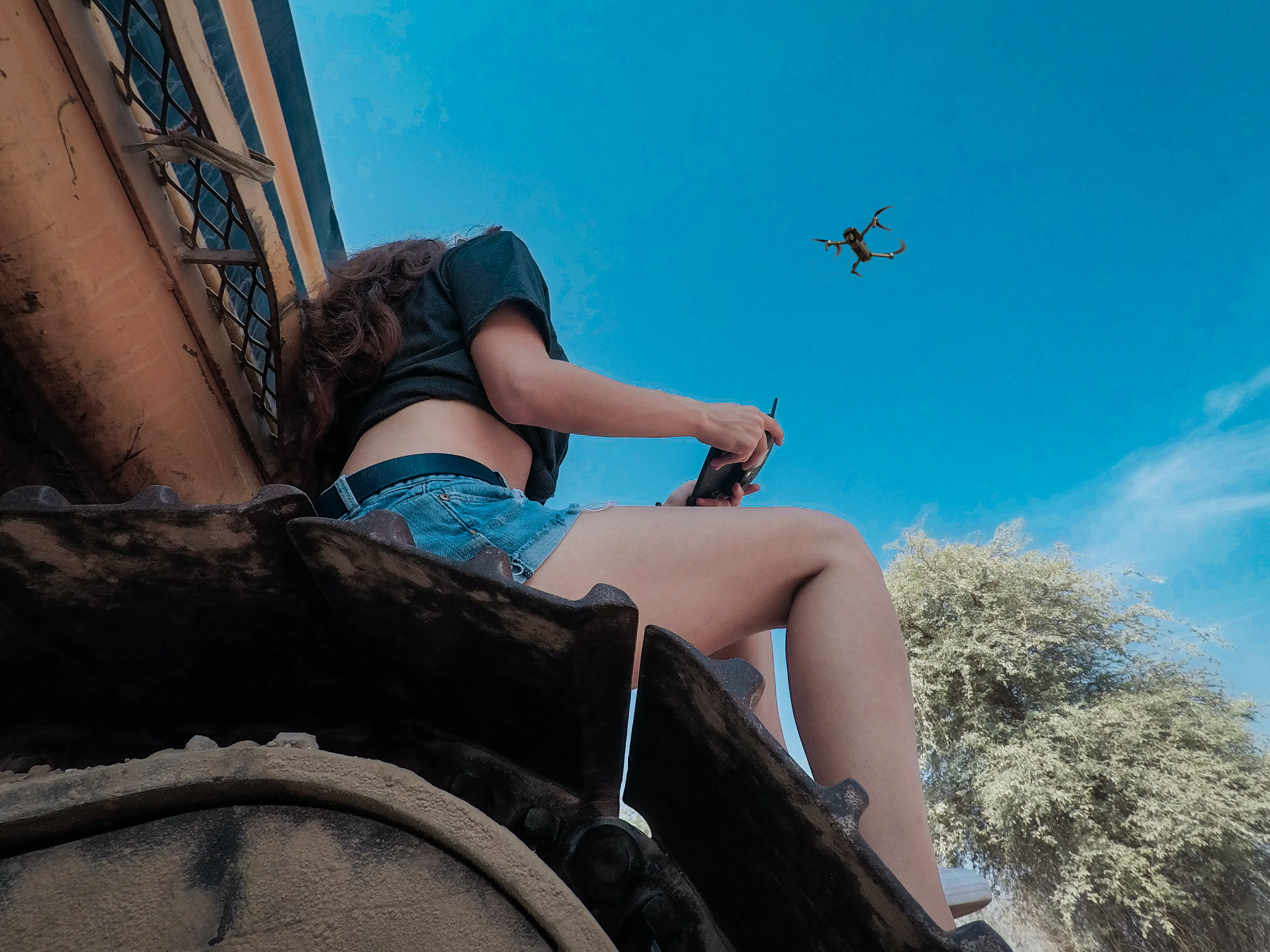 Woman Using Black Quadcopter Drone While Sitting On Roof