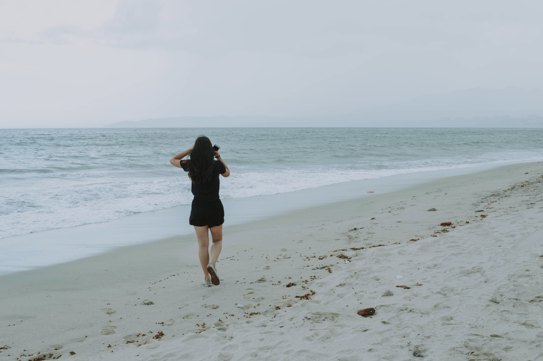 Woman Walking on White Sand Beach