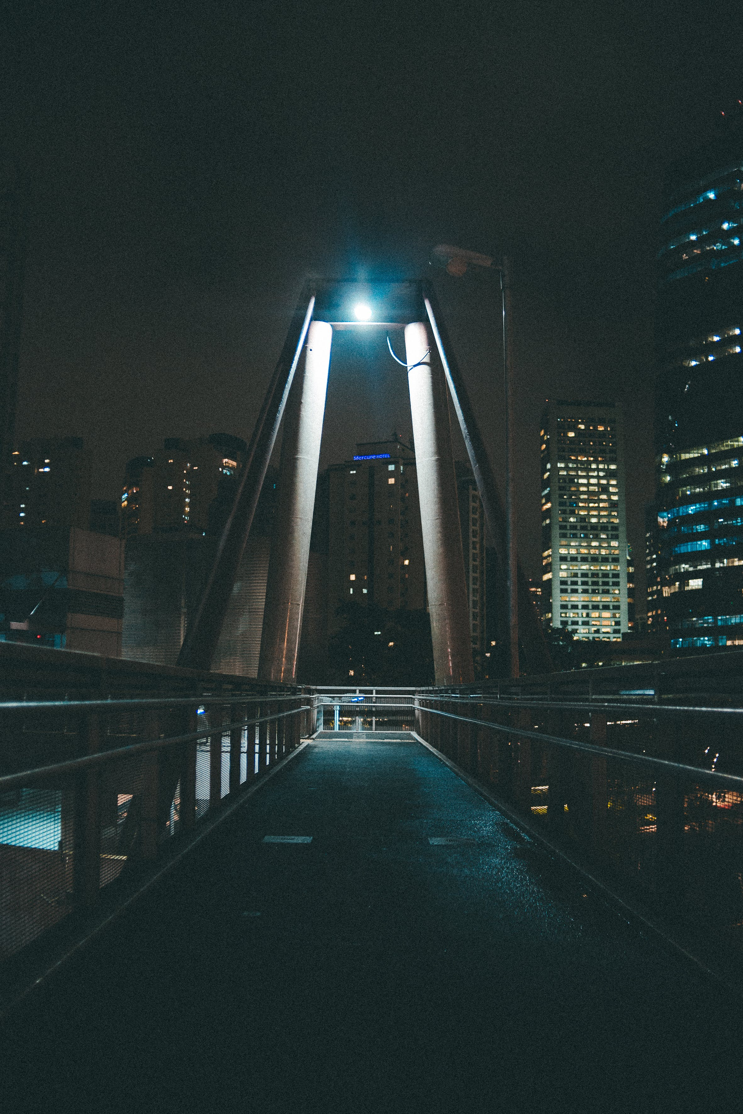 Gray Bridge Near City Buildings With Lights Turned Near at Night