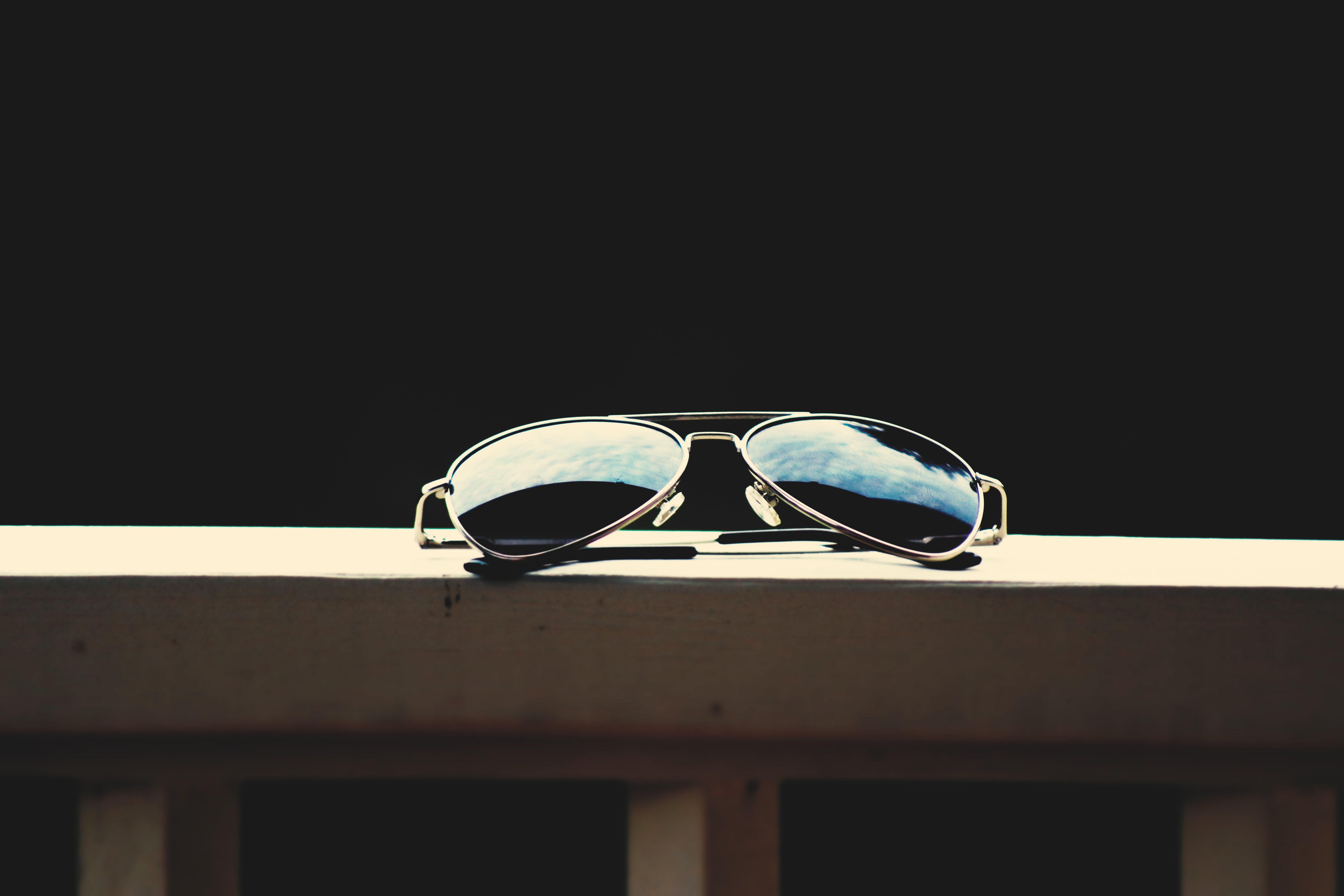 Black Lens Aviator-style Sunglasses With Gray Frames on Brown Wooden Railings