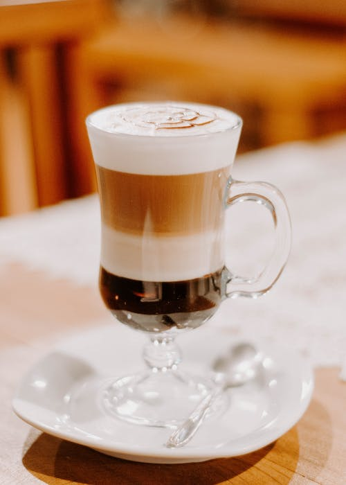 Clear Footed Drinking Glass Filled With Cappuccino on White Ceramic Saucer and Table