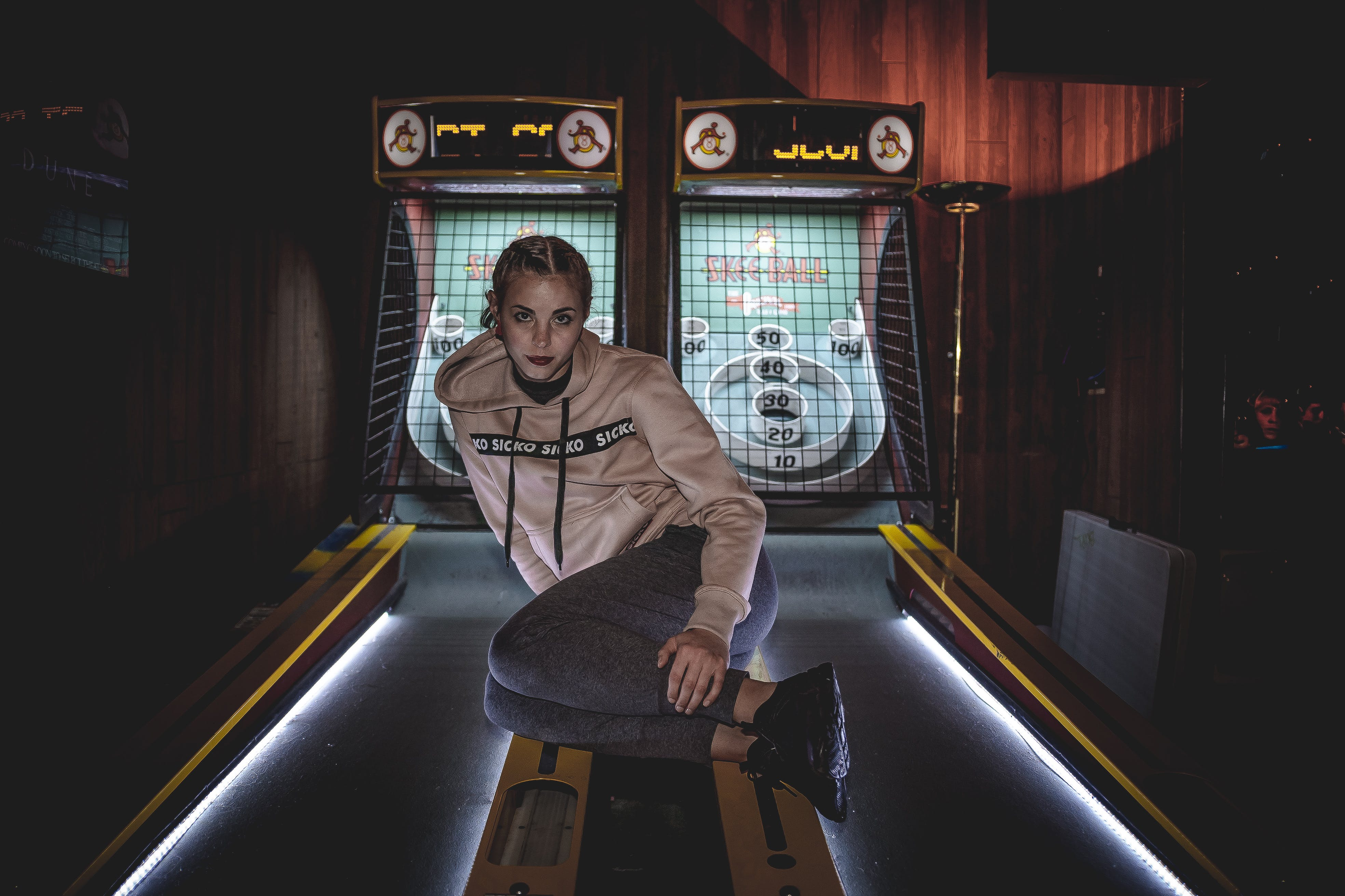 Woman in Gray Pullover Hoodie Sitting on Arcade Machine