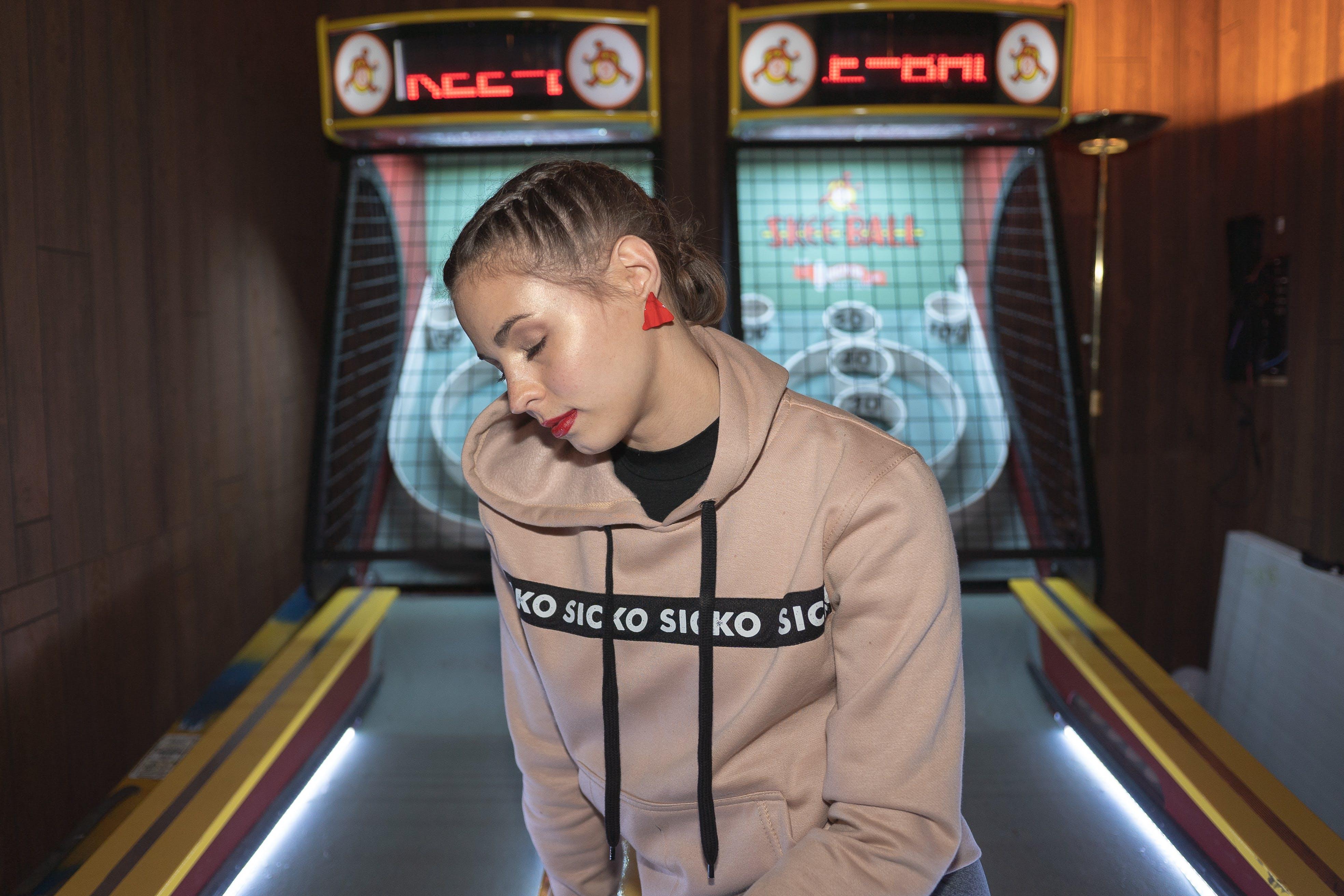 Woman Sitting on Pinball Machine