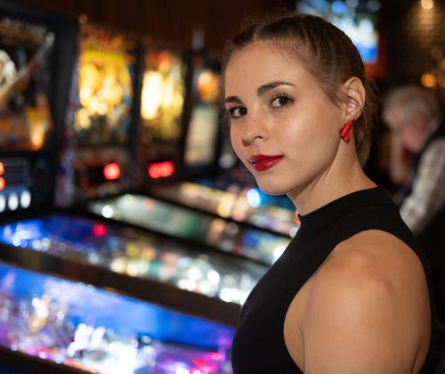 Smiling Woman Standing Near Arcade Machine