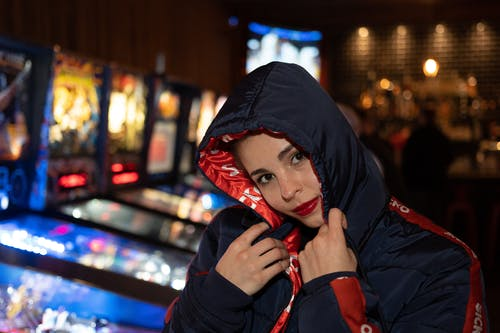 Photo of Woman in a Black and Red Jacket at an Arcade