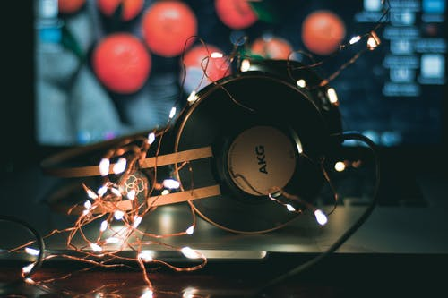 Selective Focus Photography of Black and Gray Akg Headphones With String Lights
