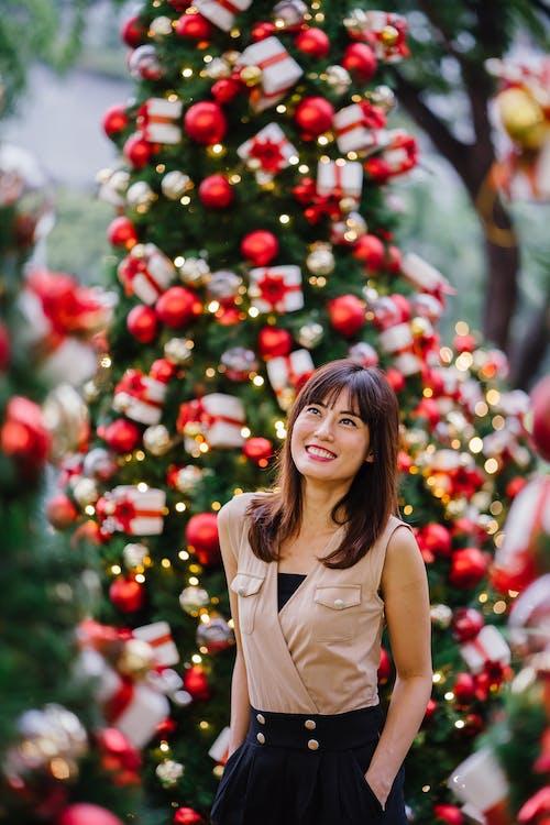 站立在圣诞树旁边的微笑的妇女选择聚焦摄影