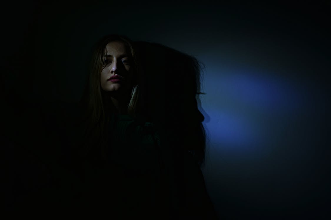 Photo of Woman in Dark Room