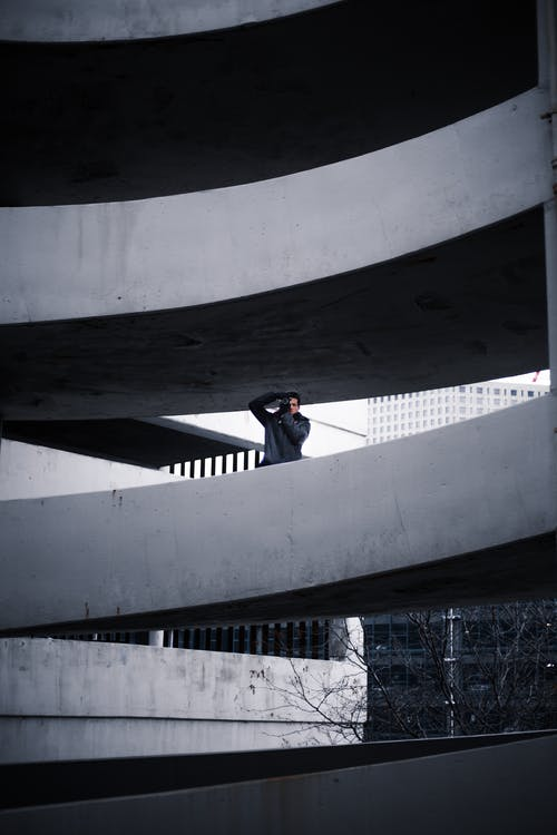 Man on Concrete Building Taking Photo