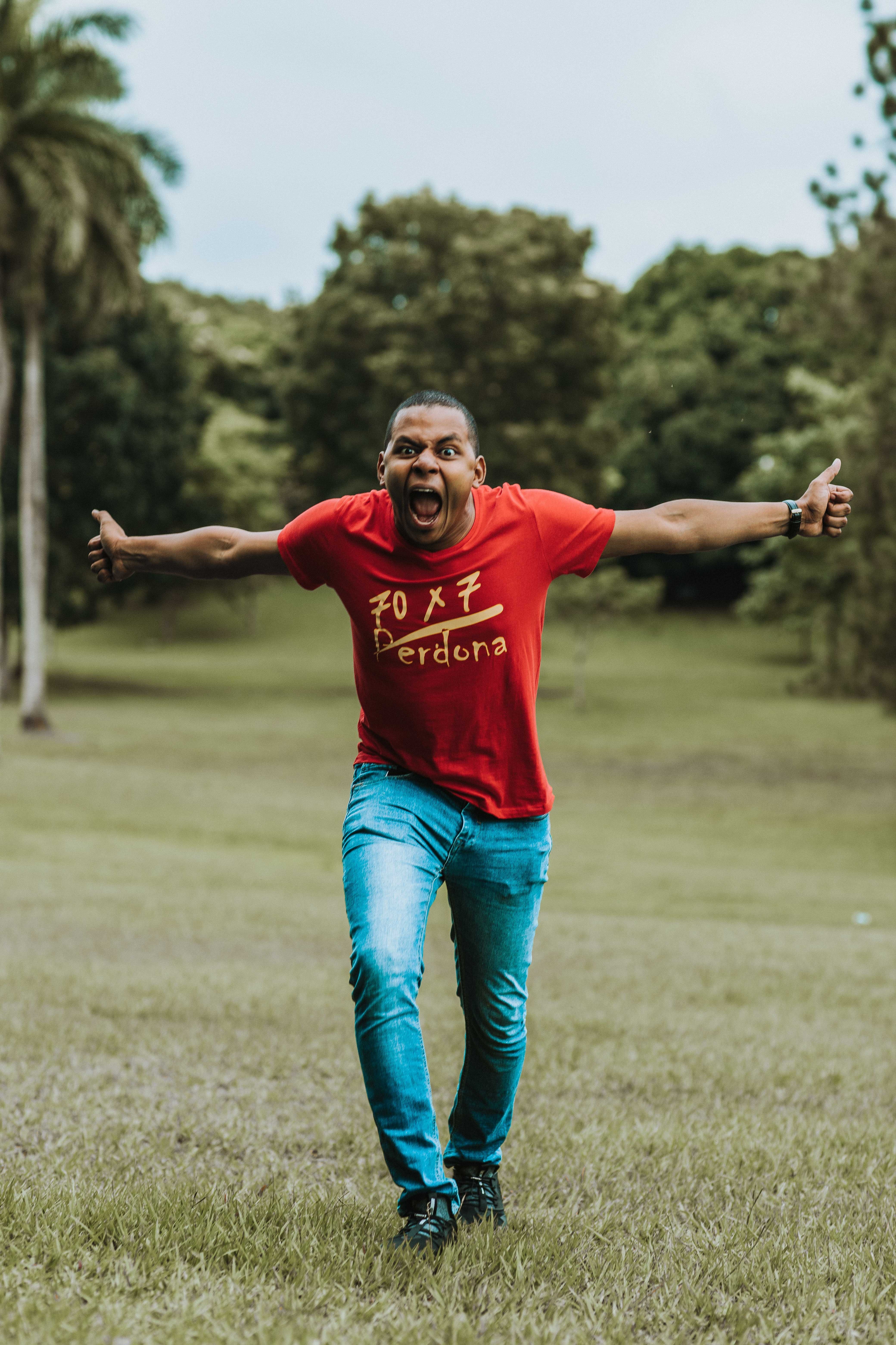 Man wearing red t-shirt and blue jeans Running on Grass
