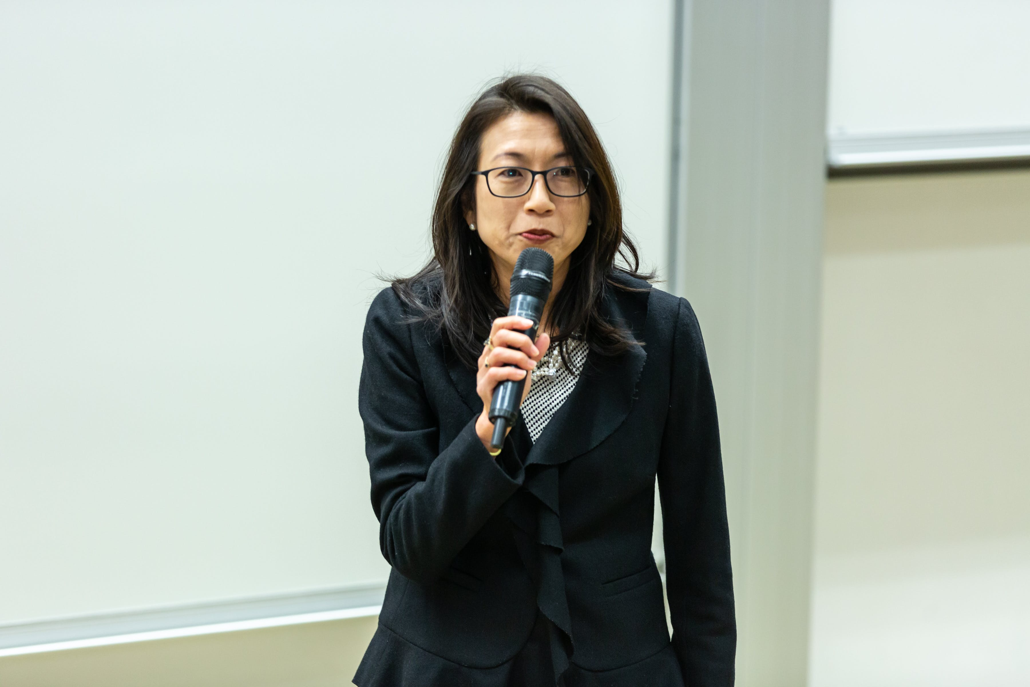 Woman Wearing Black Blazer Talking to Microphone Beside White Wall