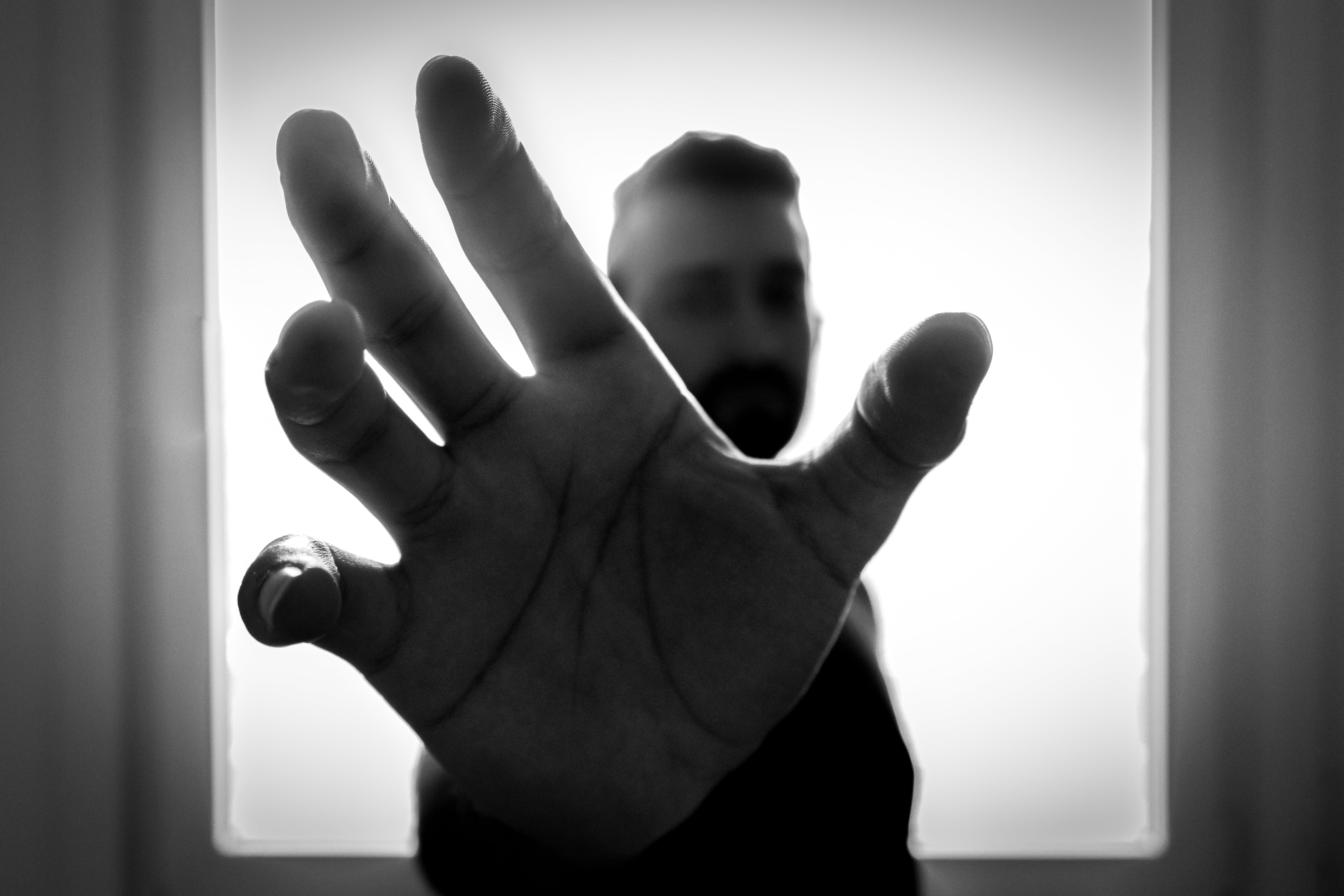 Grayscale Photo of Man Grabbing Using Right Hand