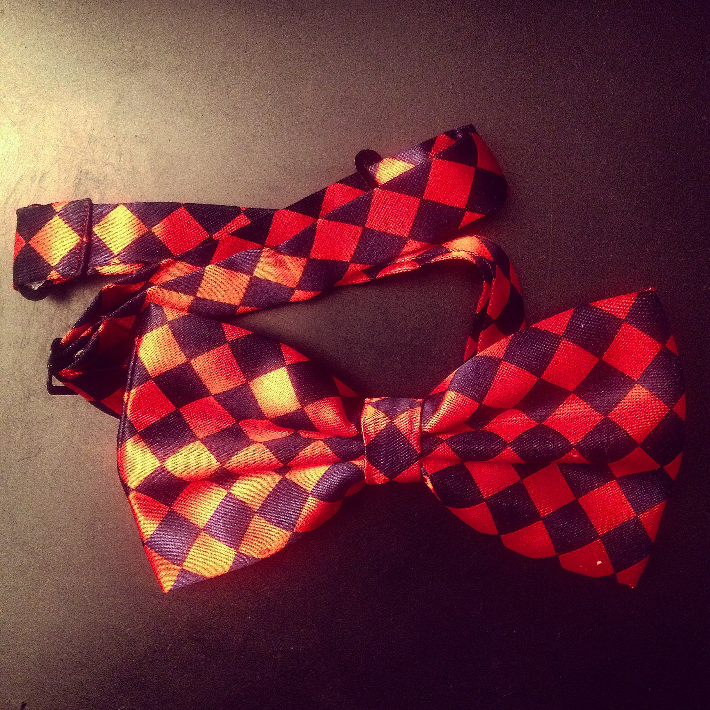 Red and Black Checkered Bow on Black Surface