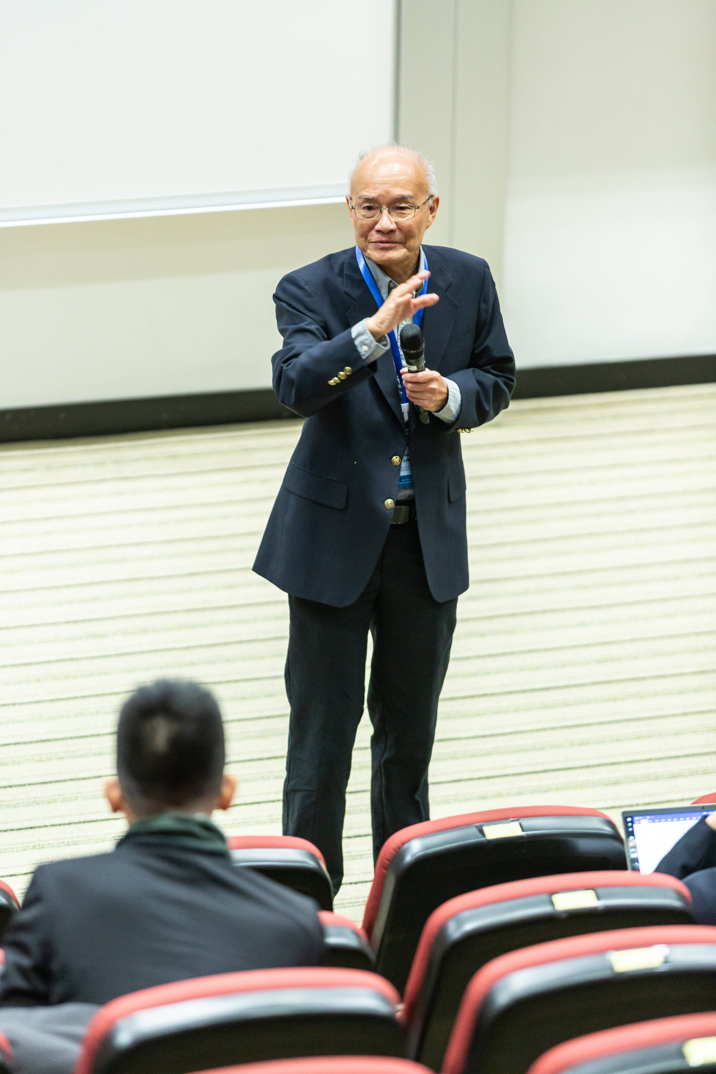 Man Standing in Front of Chairs and People
