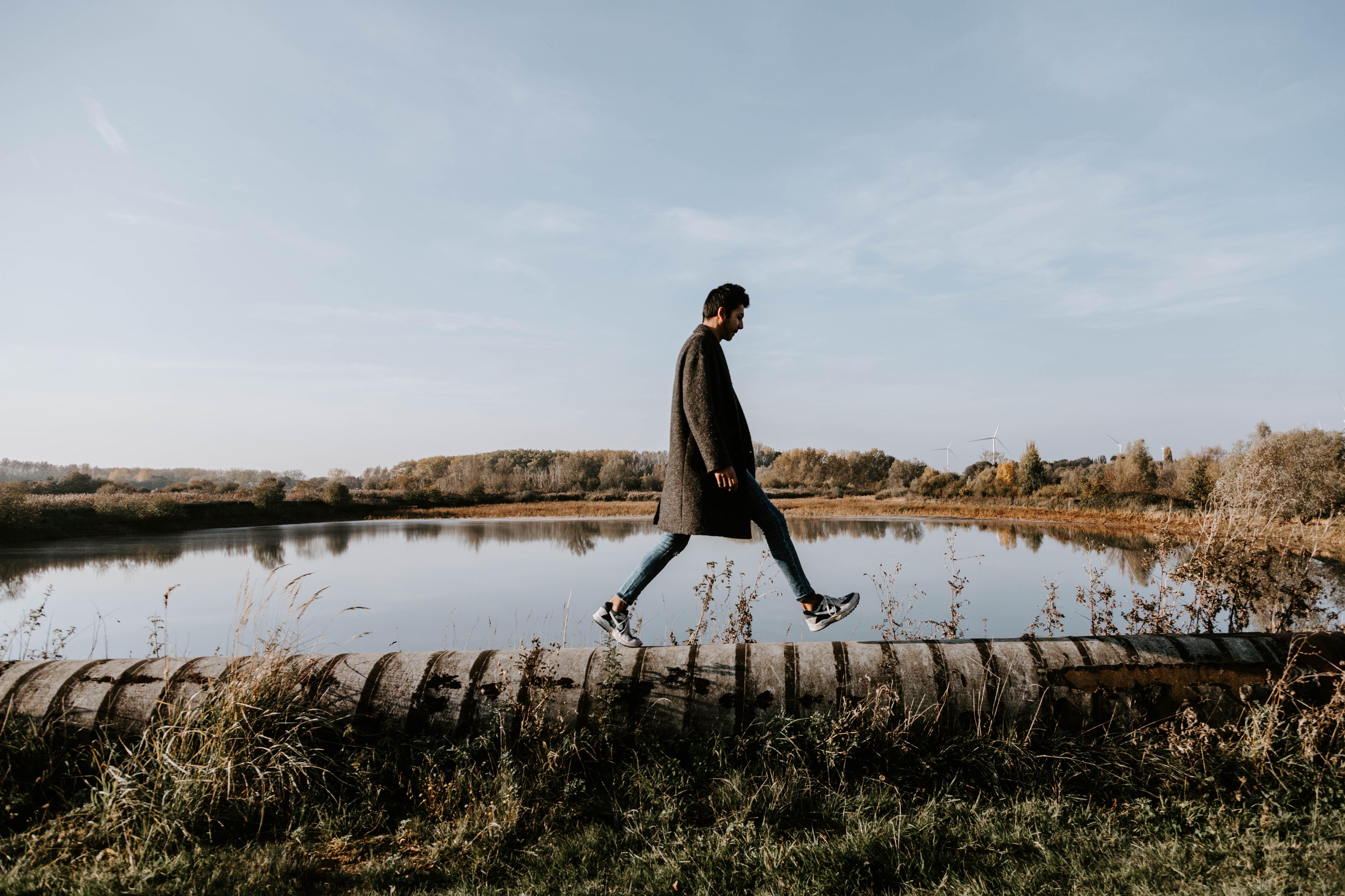 Man Walking on Concrete Pavement Near Body of Water