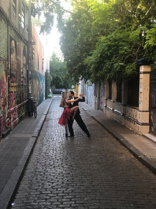 Man and Woman Dancing in Middle of Alleyway