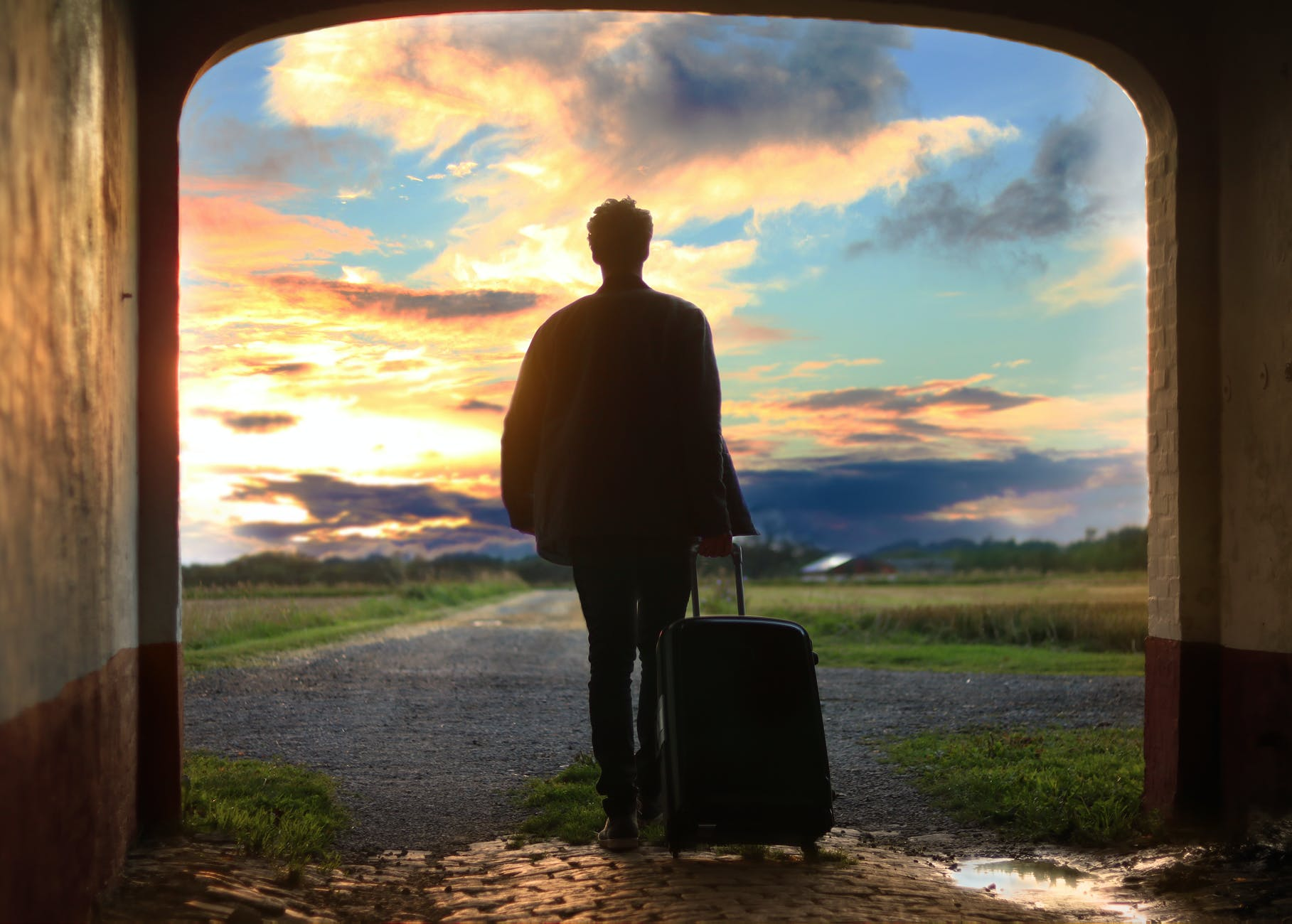 man pulling luggage walking near gray concrete road during sunset