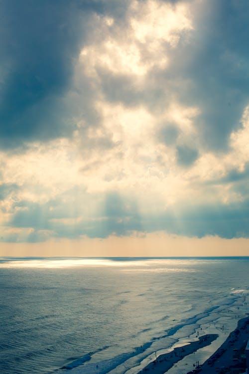 Foto stok gratis cahaya matahari, langit mendung, langit yang dramatis, lautan