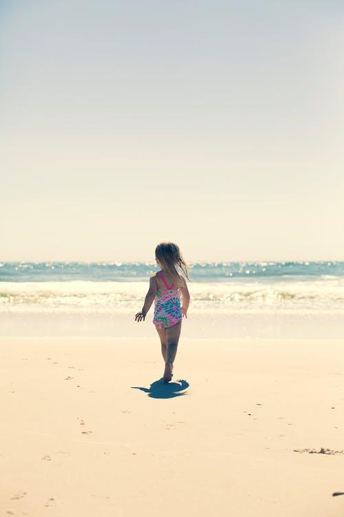 Girl Standing On Brown Sand