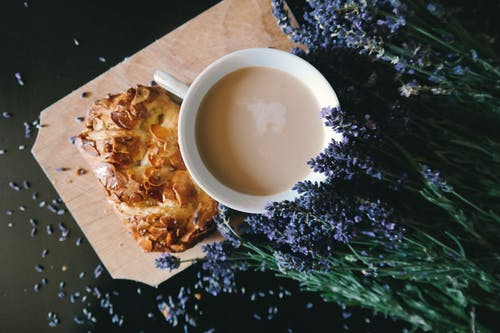White Ceramic Mug With Brown Liquid Inside Beside Purple Flower and Pastry