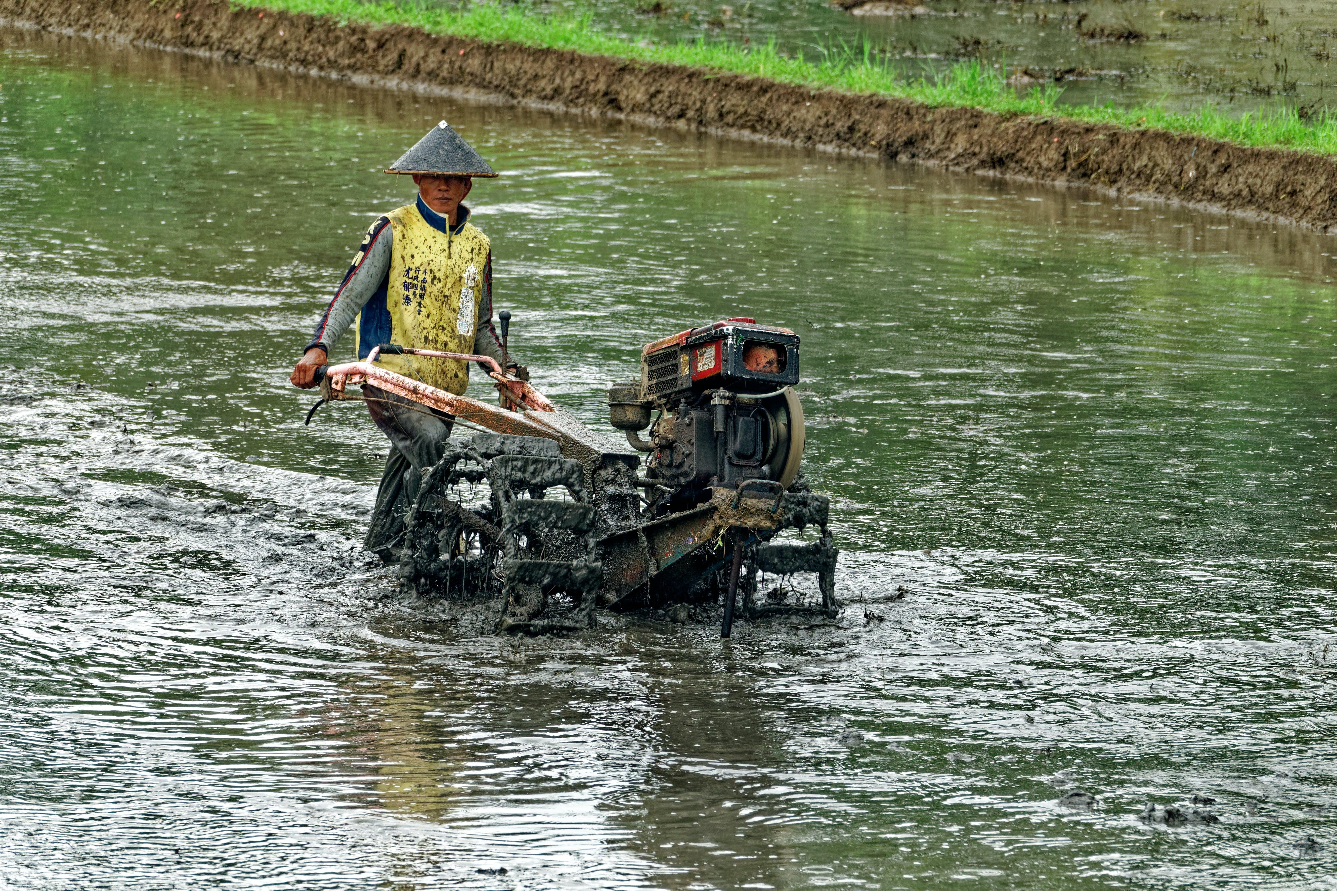 Man Pushing Wheeled Machine Into Body of Water