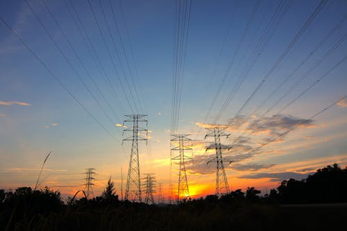 Three Black Metal Electricity Posts during Golden Hour