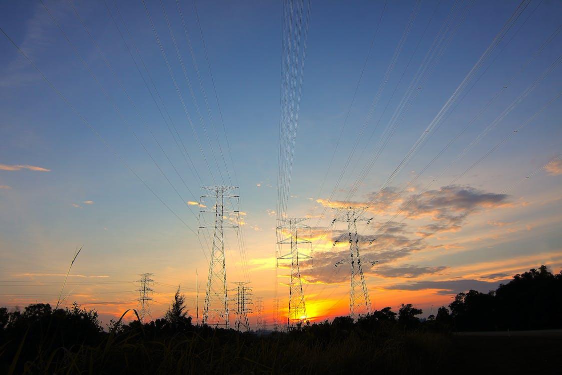 Tres Postes De Electricidad De Metal Negro Durante La Hora Dorada