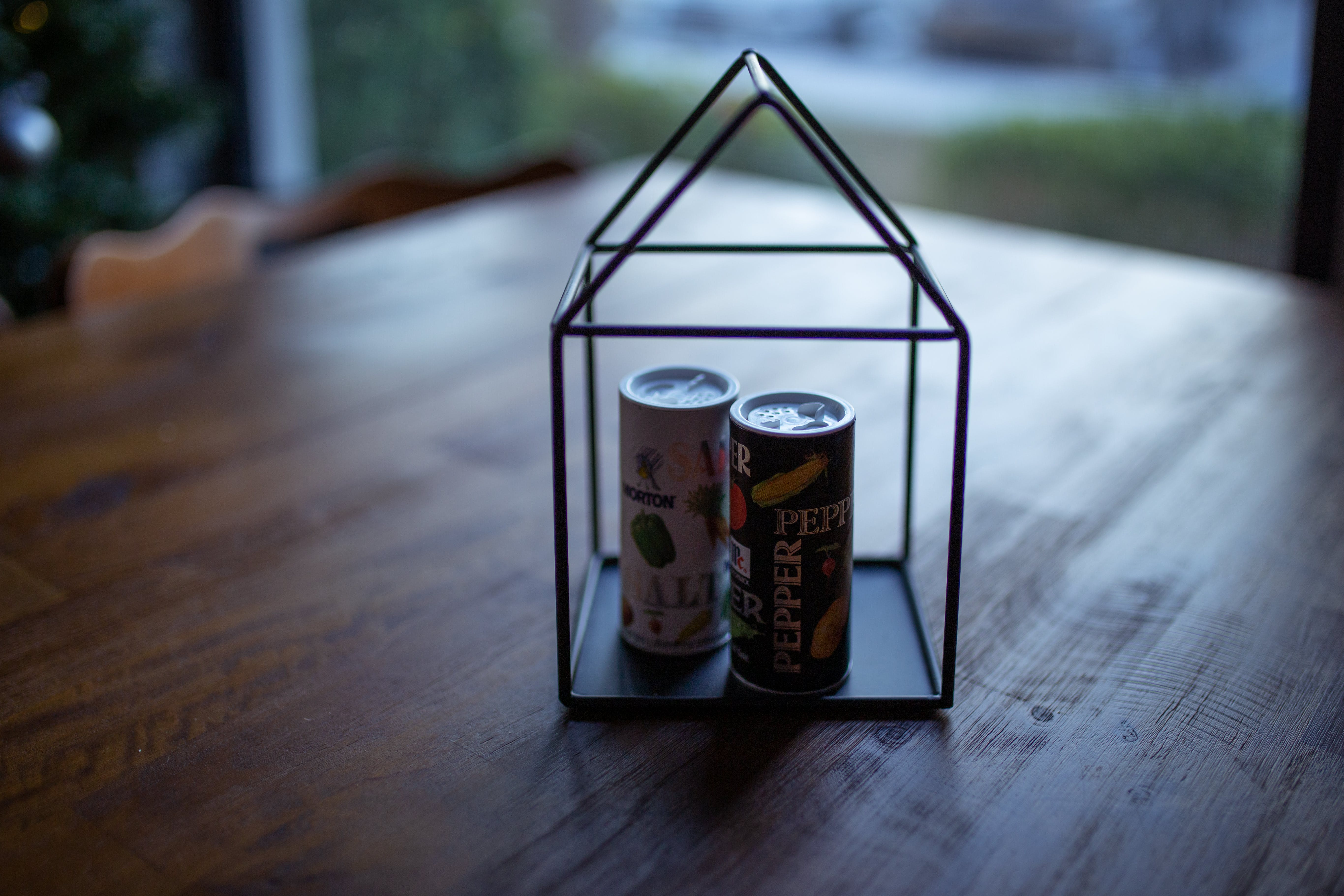 Two Labeled Thin Cans on Black Frame