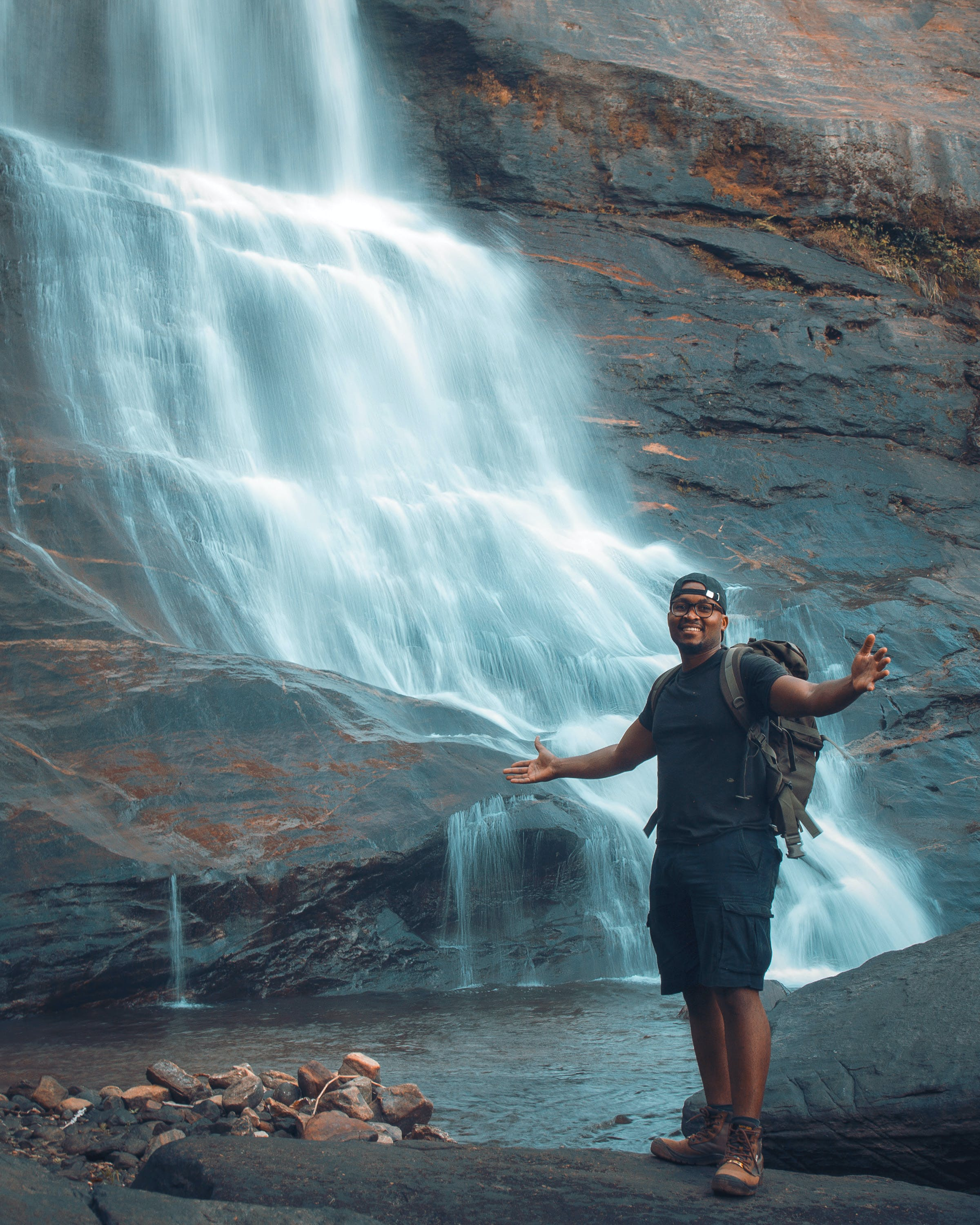 Man Standing on Rock in Front of Waterfalls