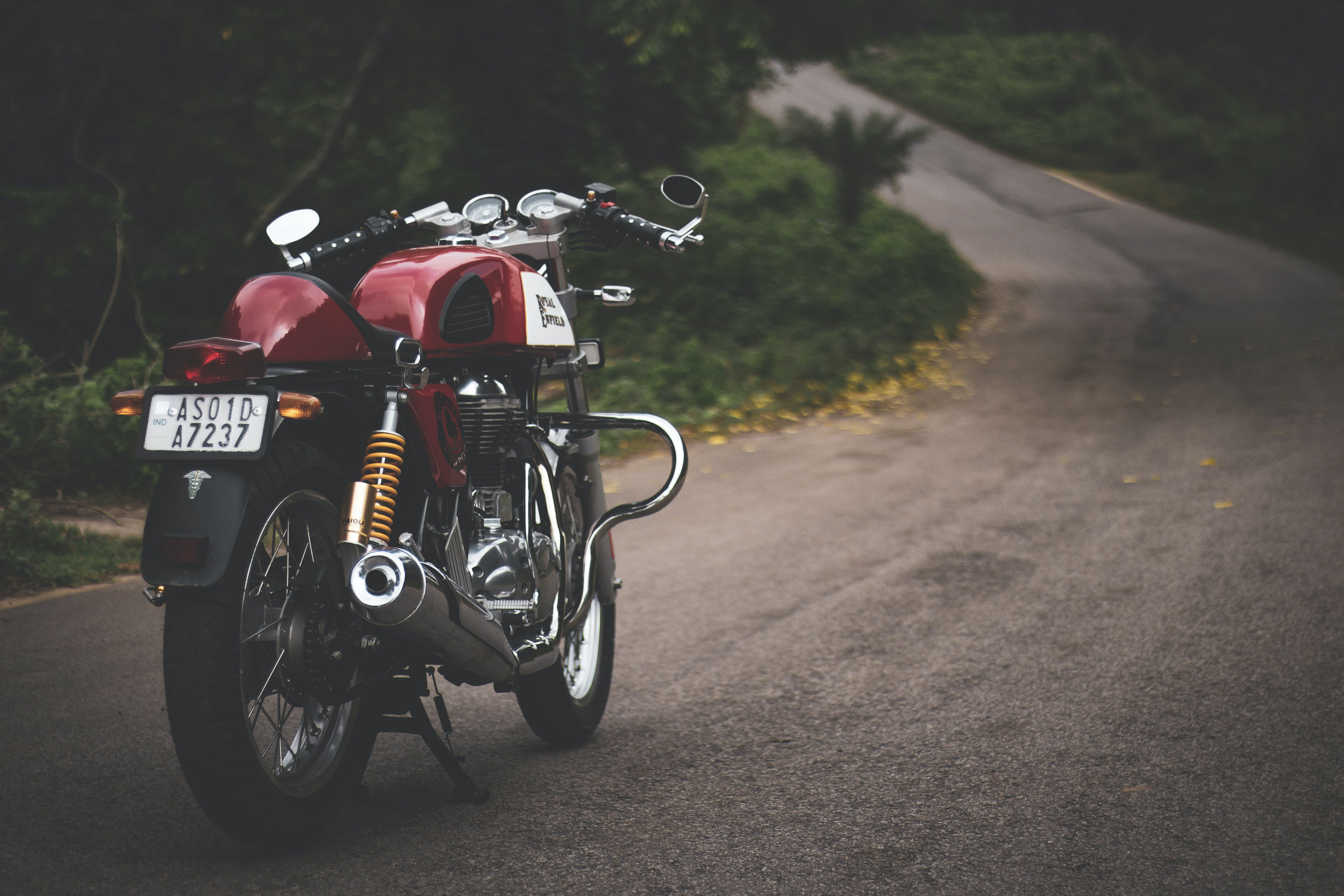 Red Standard Motorcycle Parked on Farm Road