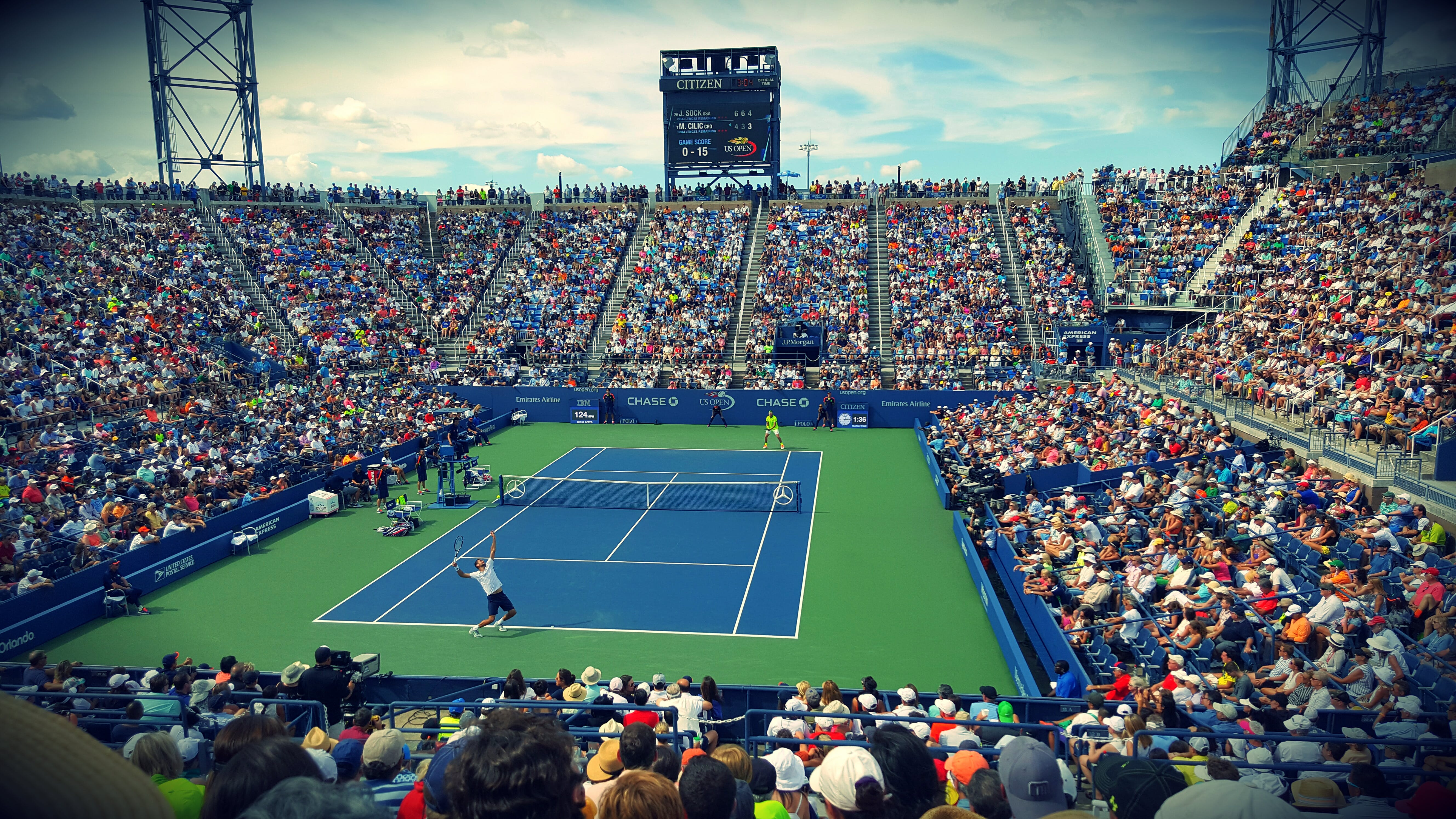 People Sitting on Bench Watching Tennis Event on Field during Daytime