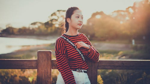 Photo of Woman in Red and Black Striped Sweater Leaning on Brown Fence