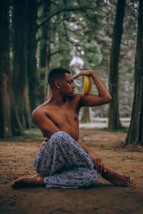 Depth Photography of Man Sitting Holding Yellow Citrus Fruit