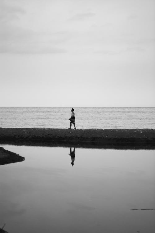 Monochrome Photograph of Man Standing Beside Water