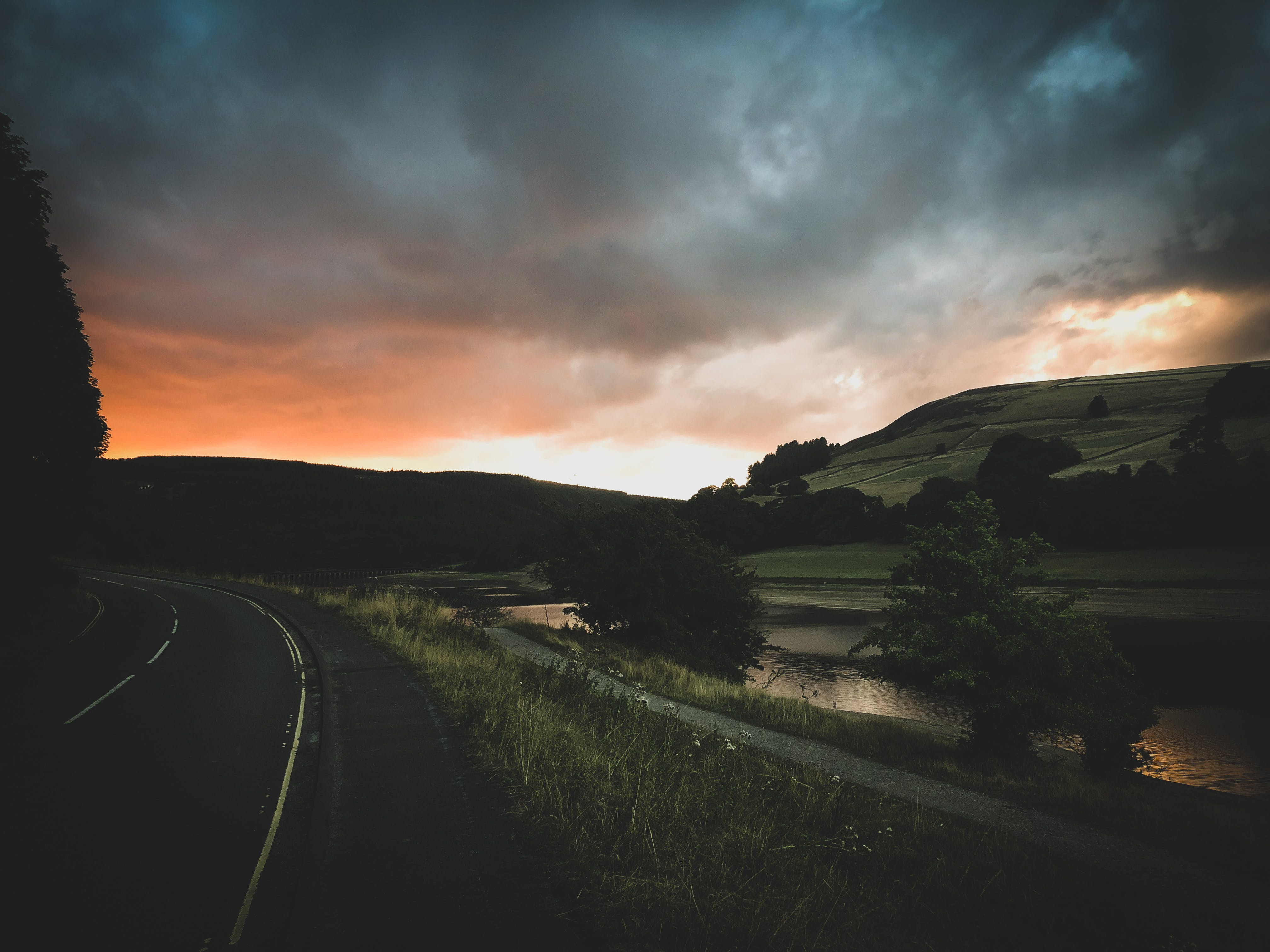 Landscape Photography of Road Beside Body of Water at Golden Hour