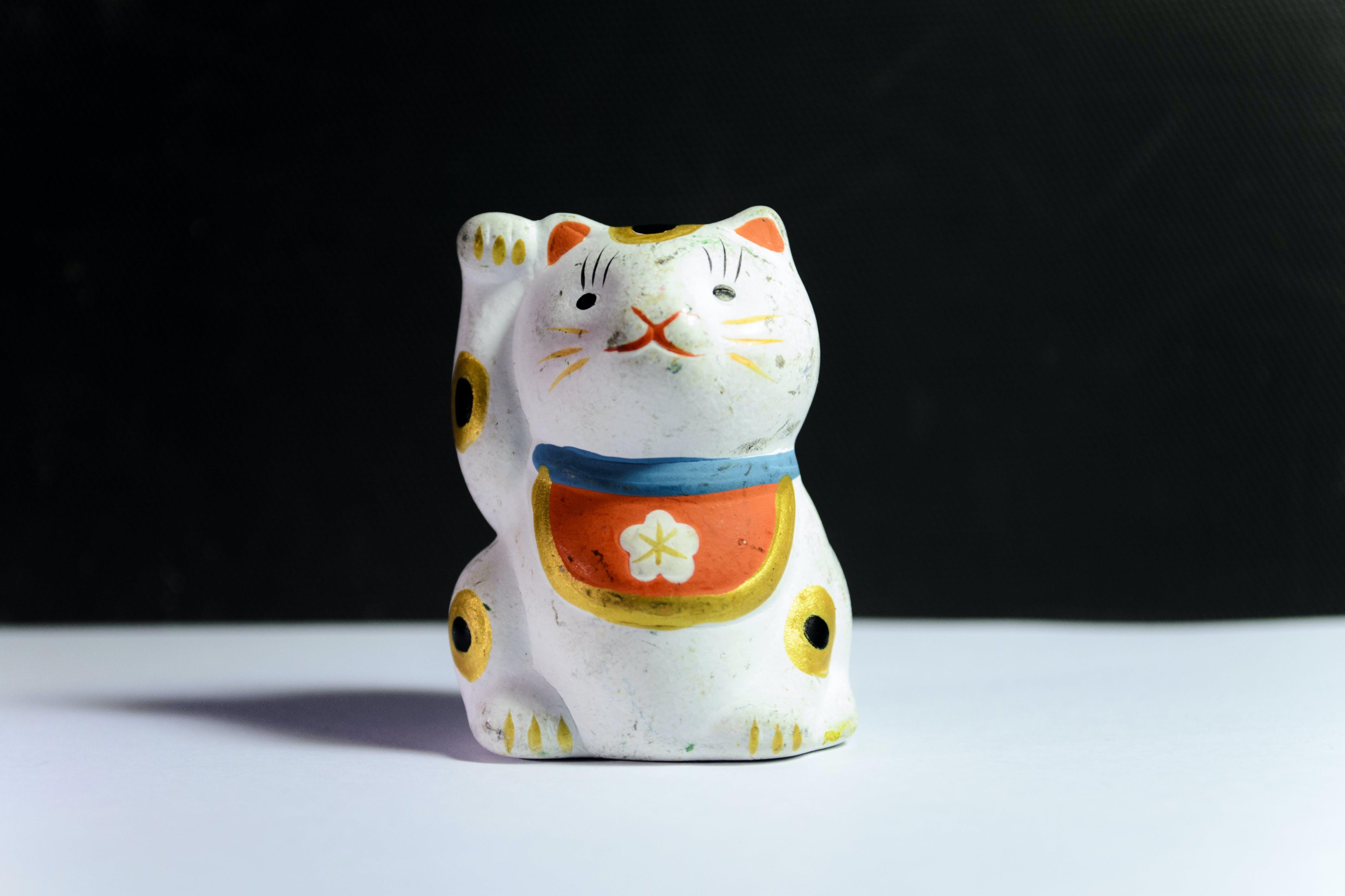 Maneki-Neko Figurine On White Surface