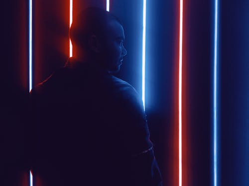 Photo of Man Standing in Front of Neon Lights