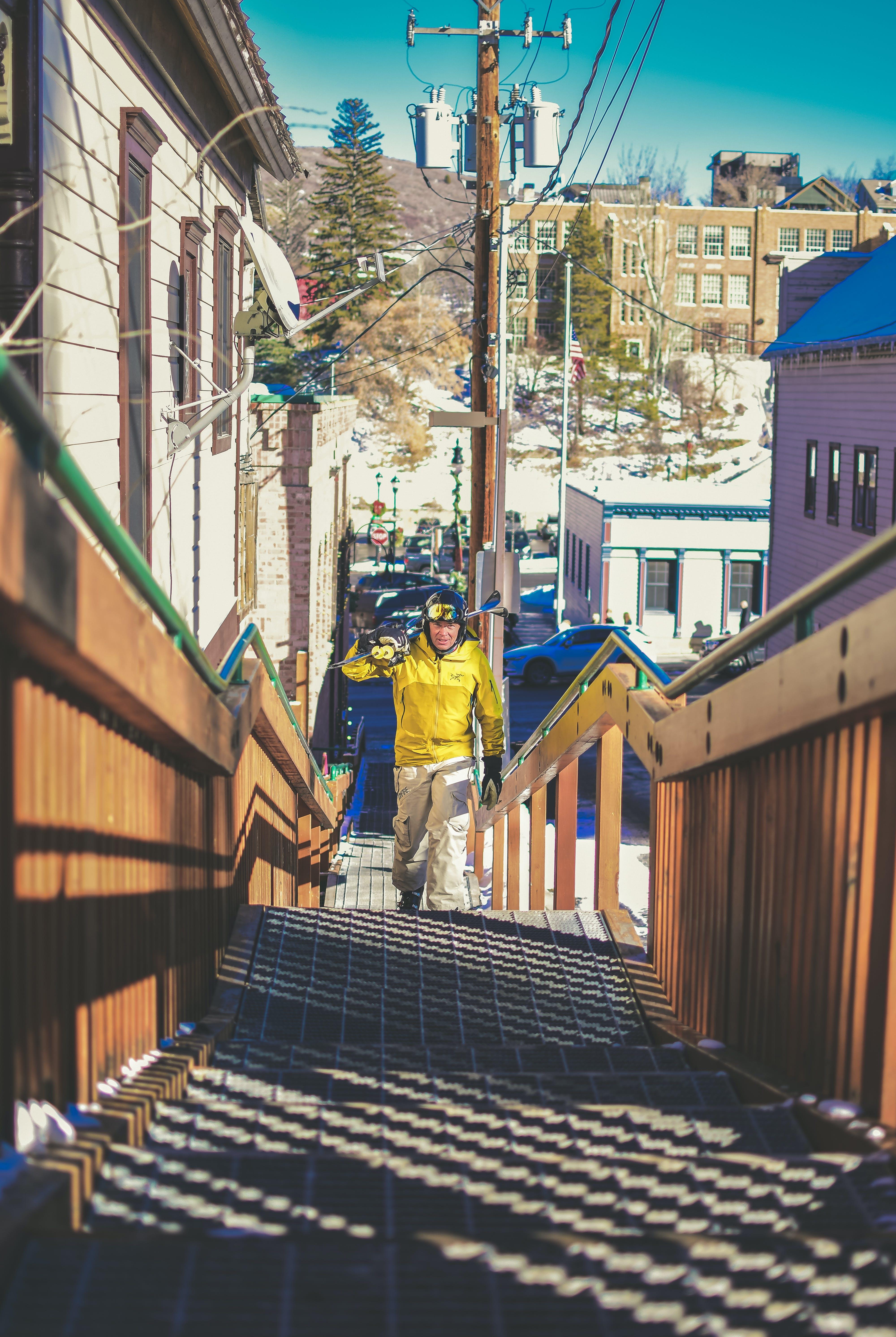 Man in Yellow Jacket Climbing Stairs