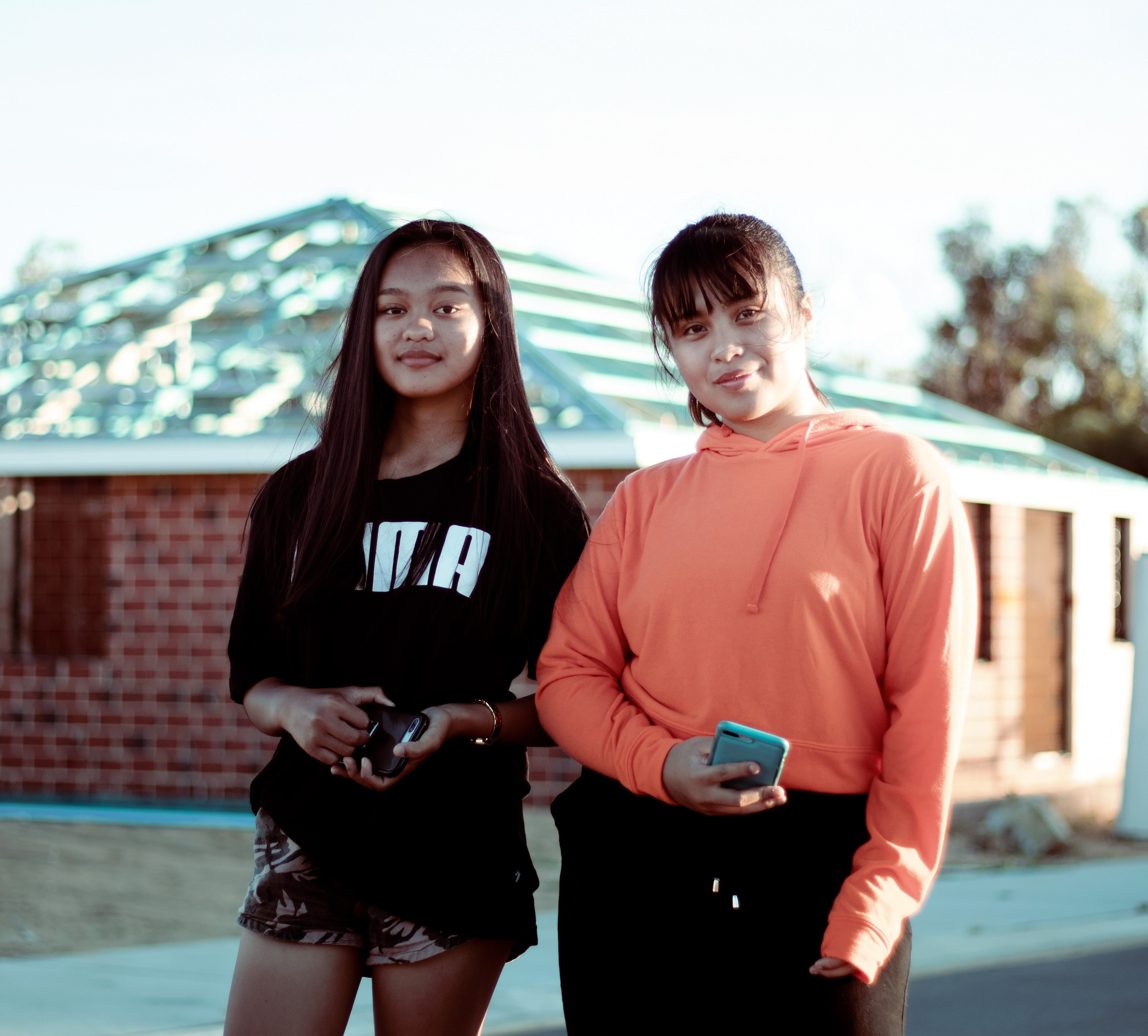 Two Women Wearing Orange Pullover Hoodie and Black T-shirt Standing in Front of Brown House