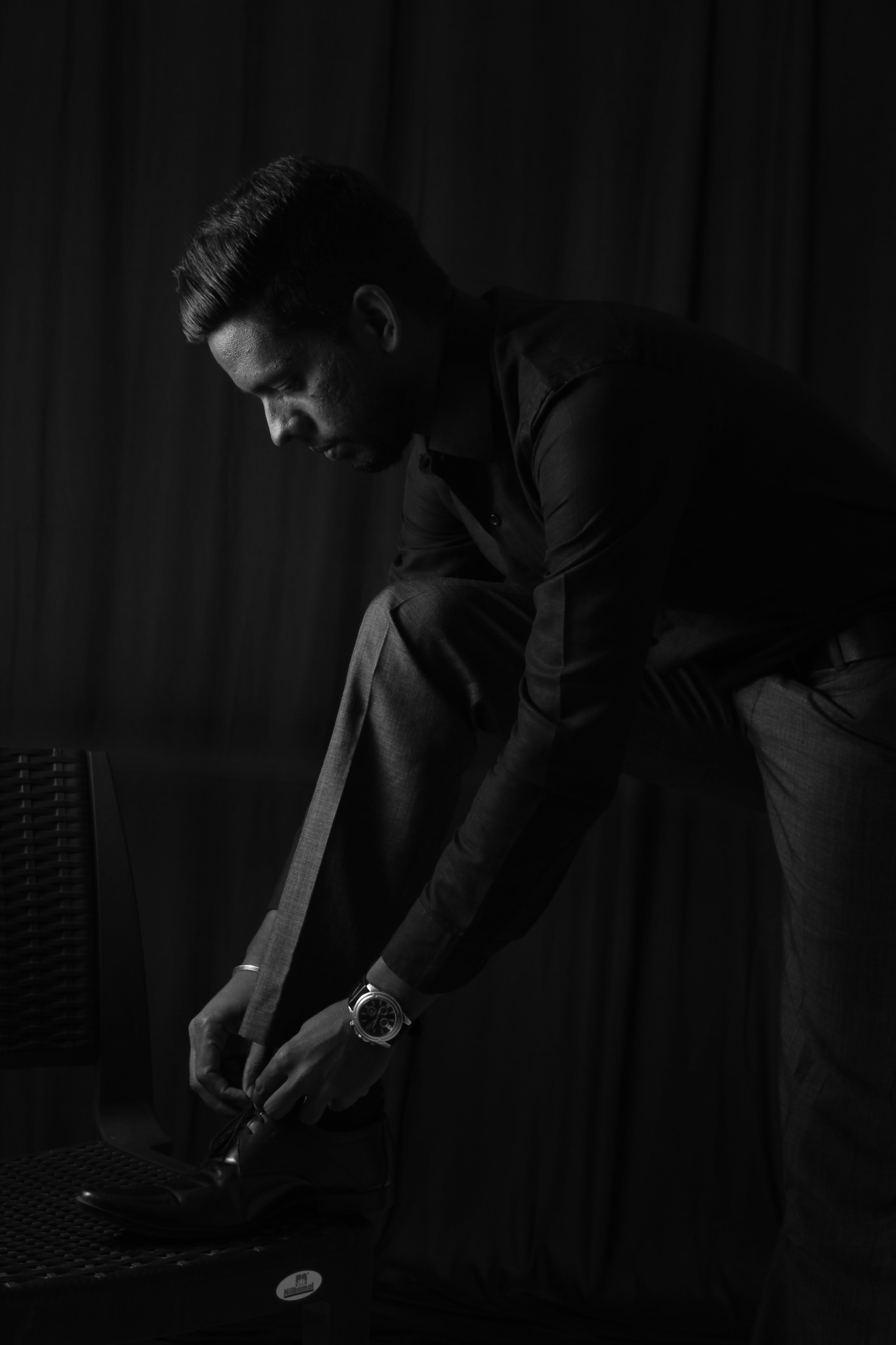 Grayscale Photo of Man in Dress Shirt and Pants Tying His Shoelaces
