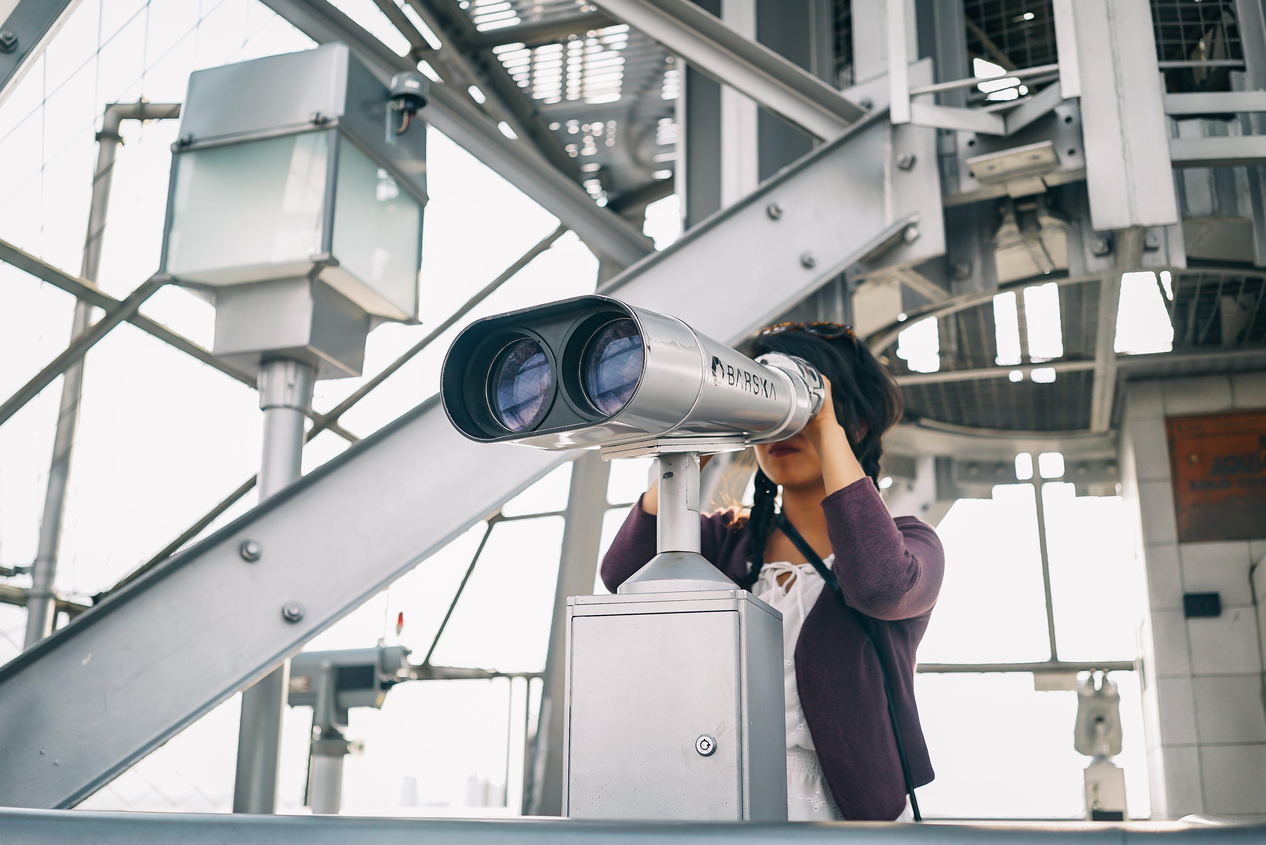 Woman in Purple Cardigan Using Binoculars