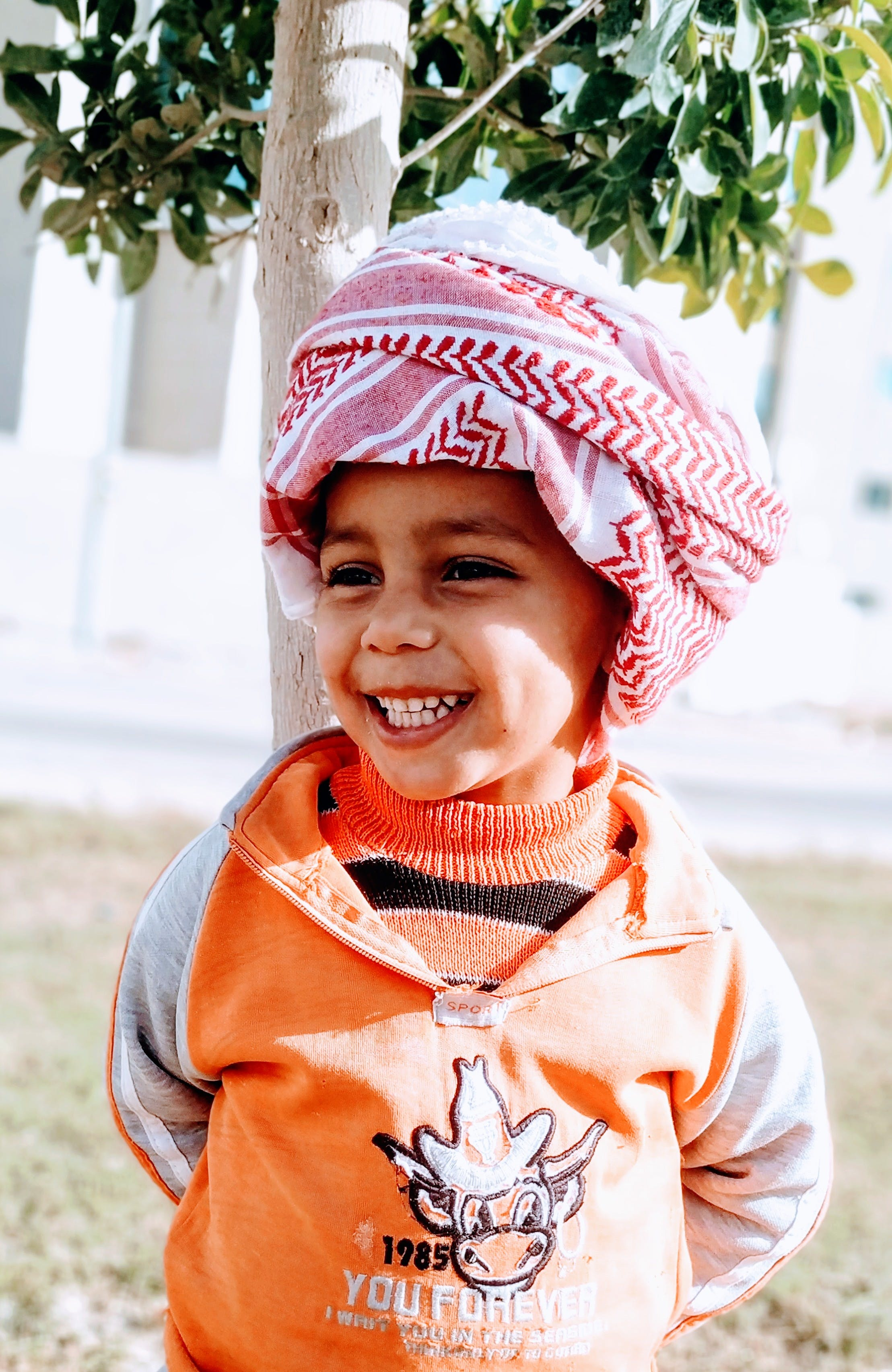 Photo of Smiling Boy in Keffiyeh Standing Near Tree