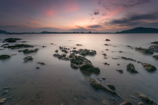 Rocks on Body of Water during Sunset