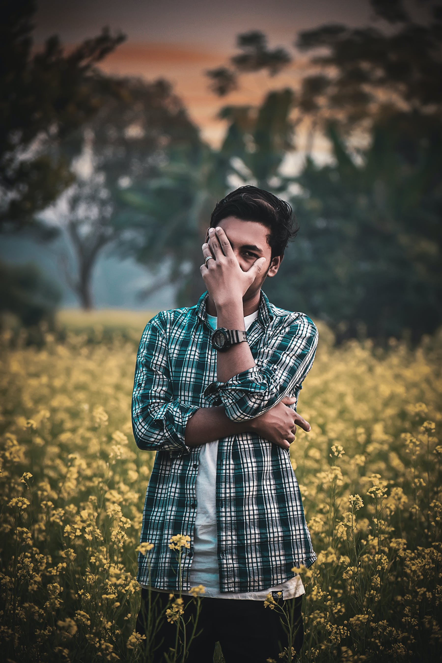 Photo of Man Standing in Flower Field Hiding Face with His Hand