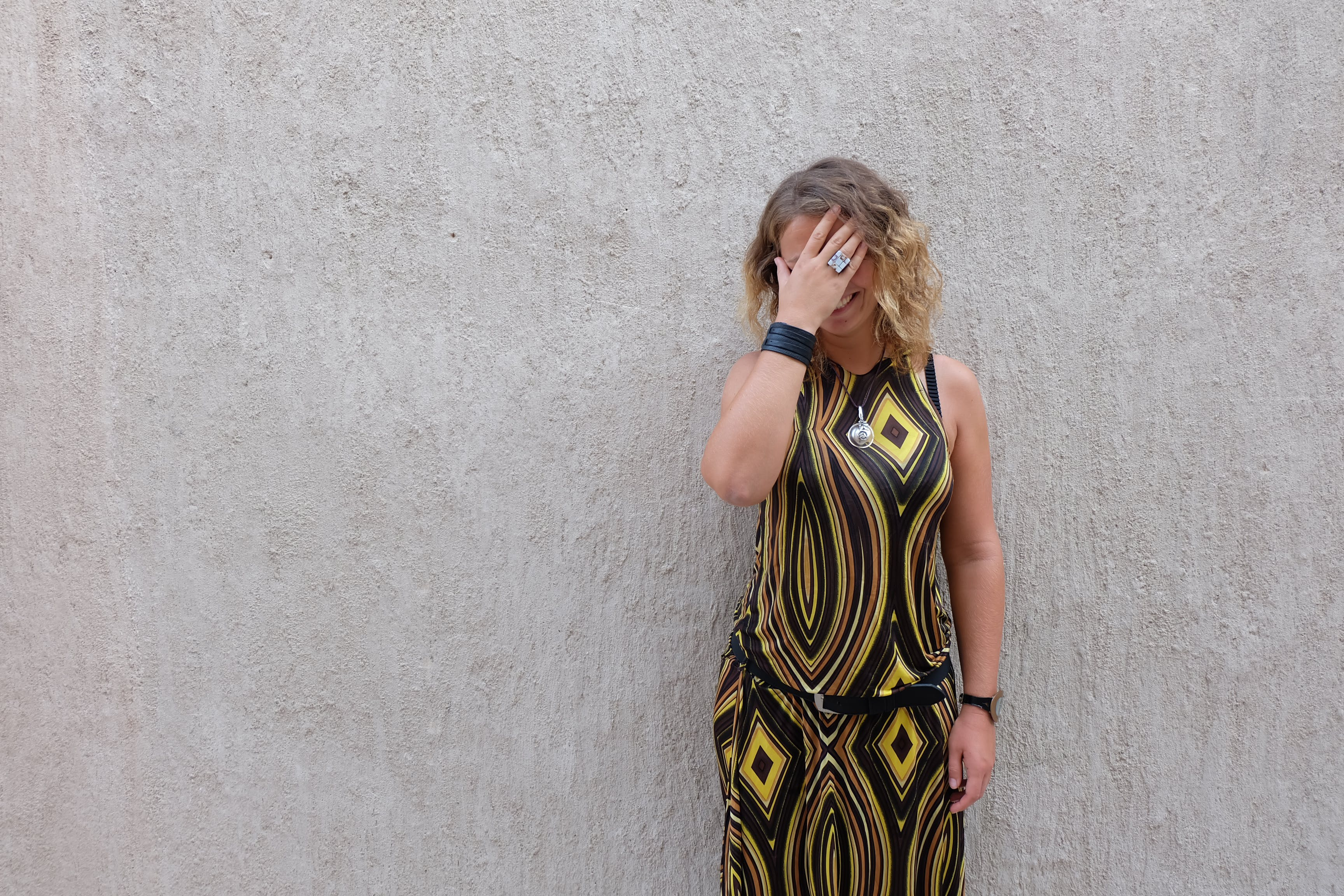 Woman Covering Face Beside Wall