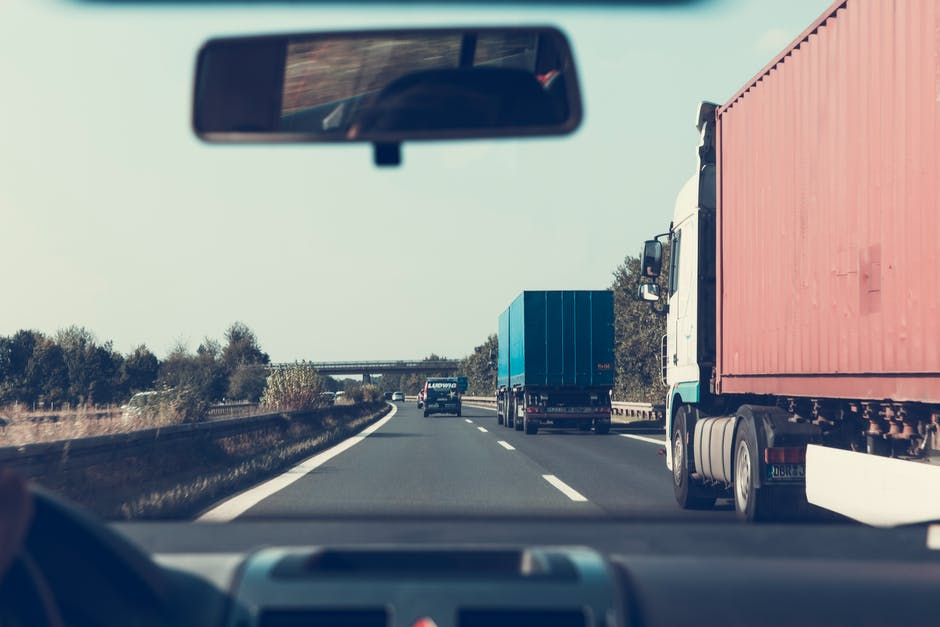 Comercial Auto Insurance for person driving besides Trailer Trucks