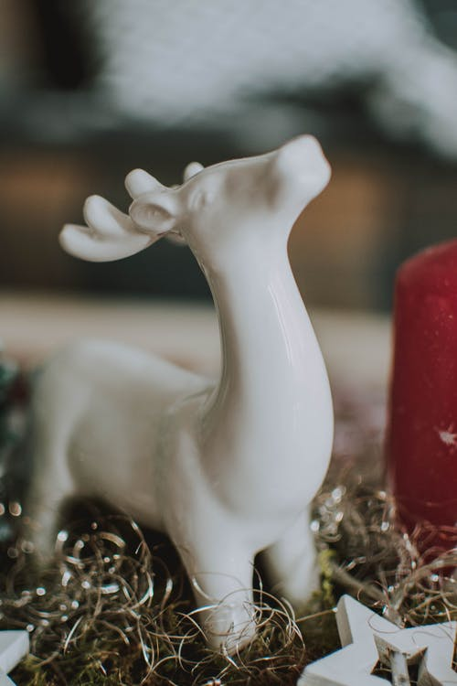 White Deer Figurine in Selective Focus Photo
